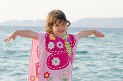 Beautiful little girl smiling at seaside in pink butterfly towel Royalty Free Stock Images