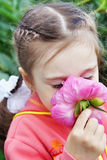 Beautiful Little Girl Sniffs a Flower in a Garden Stock Photography