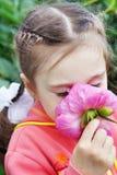 Beautiful Little Girl Sniffs a Flower in a Garden. Beautiful Little Girl Sniffs a Flower in a Summer Garden Stock Photography