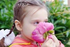 Beautiful Little Girl Sniffs Peony Flower in a Garden Stock Image
