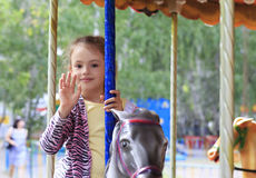 Beautiful little girl spinning on the carousel Royalty Free Stock Image