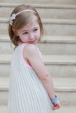 Beautiful little girl on the stairs in long dress Stock Photos