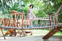 Beautiful little girl standing on hanging bridge at the playground. Beautiful little girl in dress standing on hanging bridge at the playground Royalty Free Stock Images