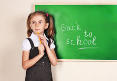 Beautiful little girl standing near blackboard Royalty Free Stock Photography