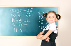 Beautiful little girl standing near blackboard Stock Photos