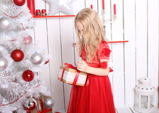 Beautiful little girl standing near the Christmas tree. The girl has blonde hair, she in a red dress magical Stock Image