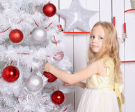 Beautiful little girl standing near the Christmas tree. The girl has blonde hair, she in a yellow dress magical. Girl hangs Christmas ball Stock Photos