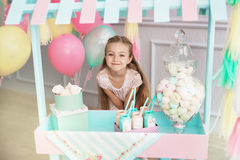 Beautiful little girl stands behind the toy candy shop Royalty Free Stock Images