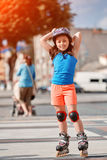 Beautiful little girl stands in roller skates at a city park in the sunshiny summer day. Cute sportive girld dressed in the colorful sportwear, with helmet and Royalty Free Stock Photo