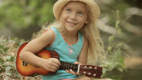 Beautiful little girl in straw hat playing on toy stock video footage