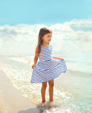 Beautiful little girl in a striped dress walking on the beach Royalty Free Stock Photo