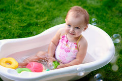 Beautiful little girl in the summer bathing with soap bubbles Royalty Free Stock Image