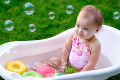 Beautiful little girl in the summer bathing with soap bubbles.  Royalty Free Stock Image