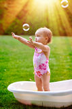 Beautiful little girl in the summer bathing with soap bubbles Stock Photography