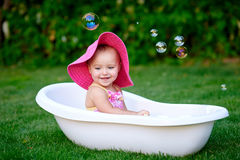 Beautiful little girl in the summer bathing with soap bubbles Stock Images