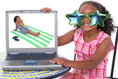 Beautiful Little Girl in Summer Dress And Crazy Sunglasses with. Laptop. Shot in studio over white with the Canon 20D Royalty Free Stock Image