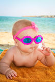 Beautiful little girl in sunglasses lies on the sea shore Stock Images