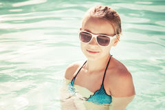 Beautiful little girl with sunglasses in outdoor pool Stock Photo