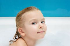 A beautiful, little girl swims in a bath with foam. Cute smiling baby. Light photo royalty free stock image