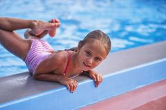 Beautiful little girl swims in the pool , cute little girl in pool in sunny day. Little girl stock photography