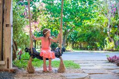 Beautiful little girl swinging on a swing in cozy Stock Image