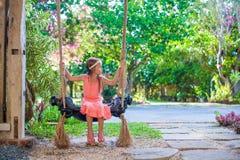 Beautiful little girl swinging on a swing in cozy Stock Image