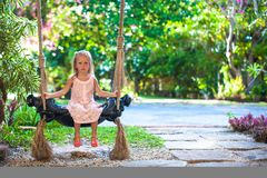 Beautiful little girl swinging on swing in a cozy Royalty Free Stock Photography