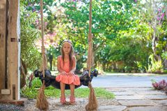 Beautiful little girl swinging on a swing in a Stock Photo
