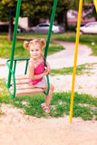 Beautiful little girl on a swings outdoor in the playground Stock Photo