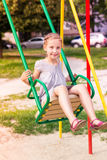 Beautiful little girl on a swings outdoor in the playground Royalty Free Stock Photo