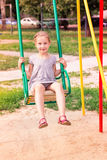 Beautiful little girl on a swings outdoor in the playground Stock Images