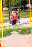 Beautiful little girl on a swings outdoor in the playground Royalty Free Stock Photography