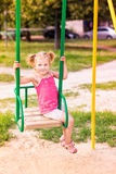 Beautiful little girl on a swings outdoor in the playground Royalty Free Stock Image