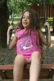 Beautiful little girl swings on the swing Royalty Free Stock Photography