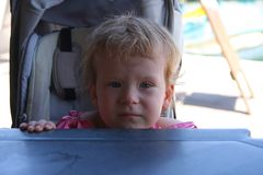 Beautiful little girl by the table. Beautiful little girl tried to reach the table from her push chair royalty free stock images
