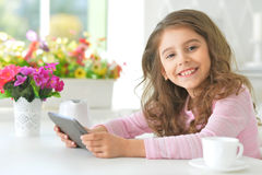 Beautiful little girl with tablet pc Stock Photo