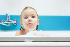 Beautiful, little girl taking a bath with foam. The child looks at the camera in surprise. Light photo royalty free stock image