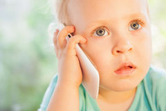 Beautiful little girl talking by mobile phone with her mother Royalty Free Stock Photo