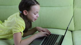 Beautiful little girl talking and typing on laptop stock video footage