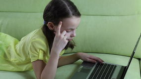 Beautiful little girl talking and typing on laptop stock footage
