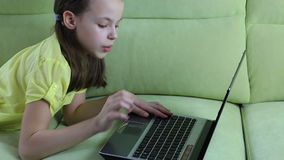 Beautiful little girl talking and typing on laptop. stock video footage