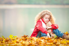 Beautiful little girl with teddy bear. Beautiful and sad little girl hugging teddy bear. Looking away from the camera. Sitting at the shore of the lake. Yellow Stock Images