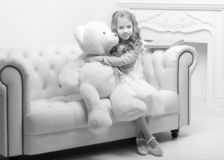 Little girl with a teddy bear in black and white photo. Beautiful little girl with a teddy bear, studio black and white photo. Concept of happy children, style royalty free stock photo