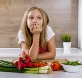 Beautiful little girl thinking about cooking. Royalty Free Stock Photo