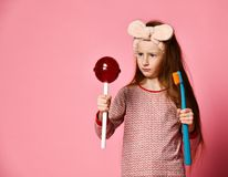 Beautiful little girl with toothbrush and sweet lolipops royalty free stock photos