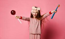 Beautiful little girl with toothbrush and sweet lolipops stock images