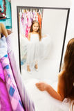 Beautiful little girl try dress before the mirror Royalty Free Stock Photo