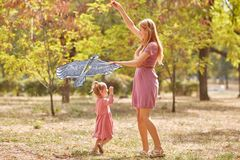 Mother and daughter having fun on a park background. Family flying a kite. Motherhood concept. Copy space. royalty free stock images