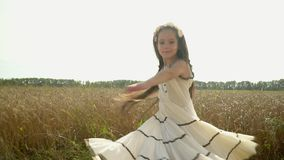 The beautiful little girl is turned in a beautiful long dress in the field of mature wheat. The lovely little girl has stock video footage