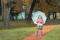 Beautiful little girl with umbrella in park Stock Images